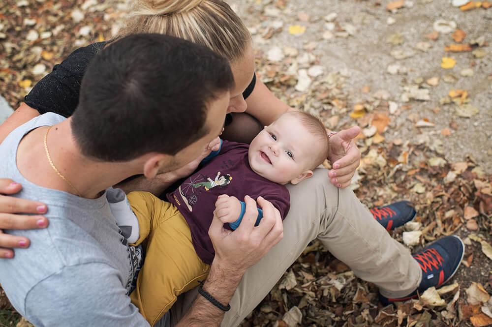 Portrait de bébé souriant sur les genoux de papa.