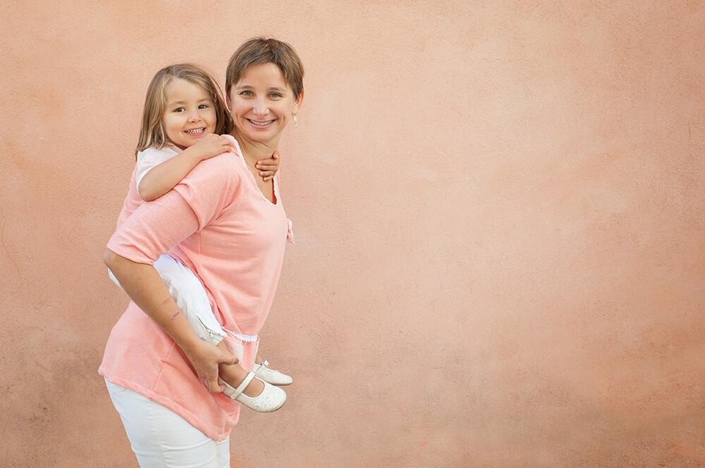Enfant sur le dos de sa maman. Portrait ton sur ton.