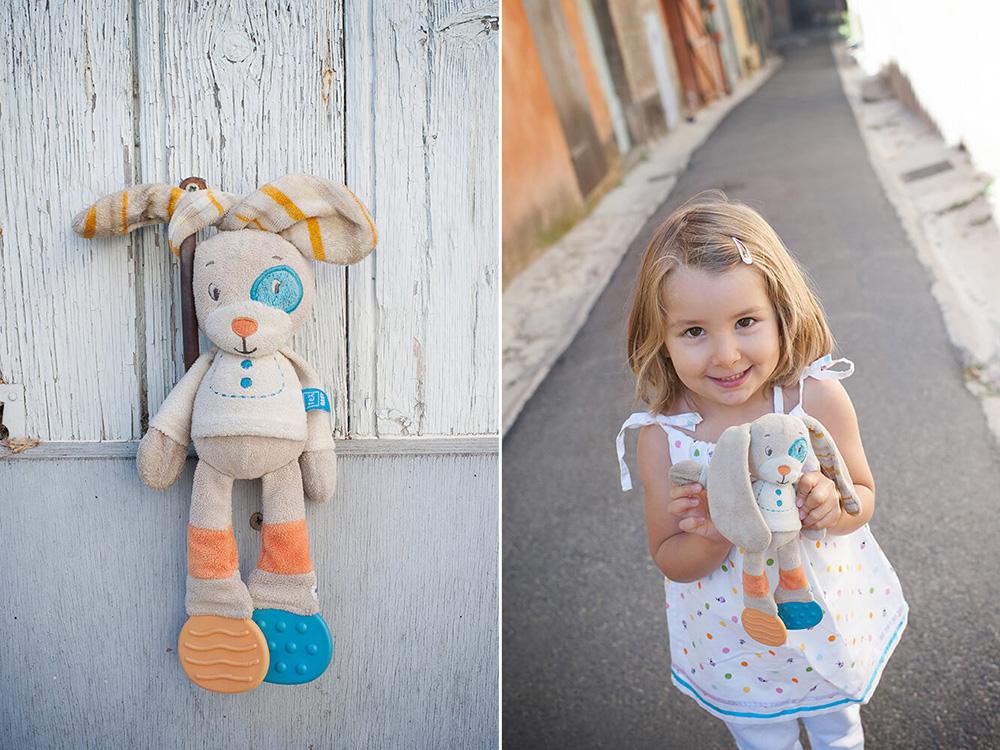 Portrait d'une jeune fille tenant son doudou dans les main.