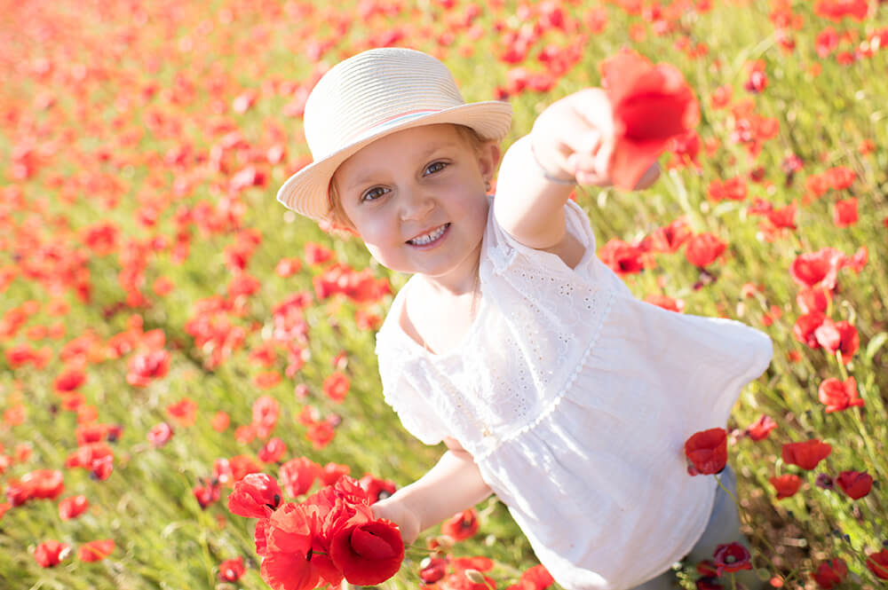 Portrait enfant dans un champ de coquelicot. Séance photo lifestyle.