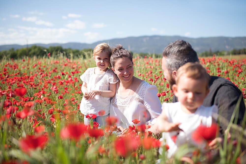 Séance photo famille dans un champ de coquelicots.