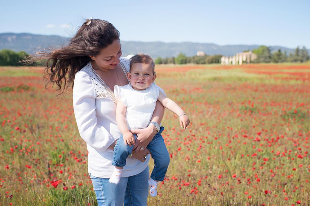 Portrait de bébé d'un an dans les bras de sa maman et au milieu d'un énorme champ de coquelicots.