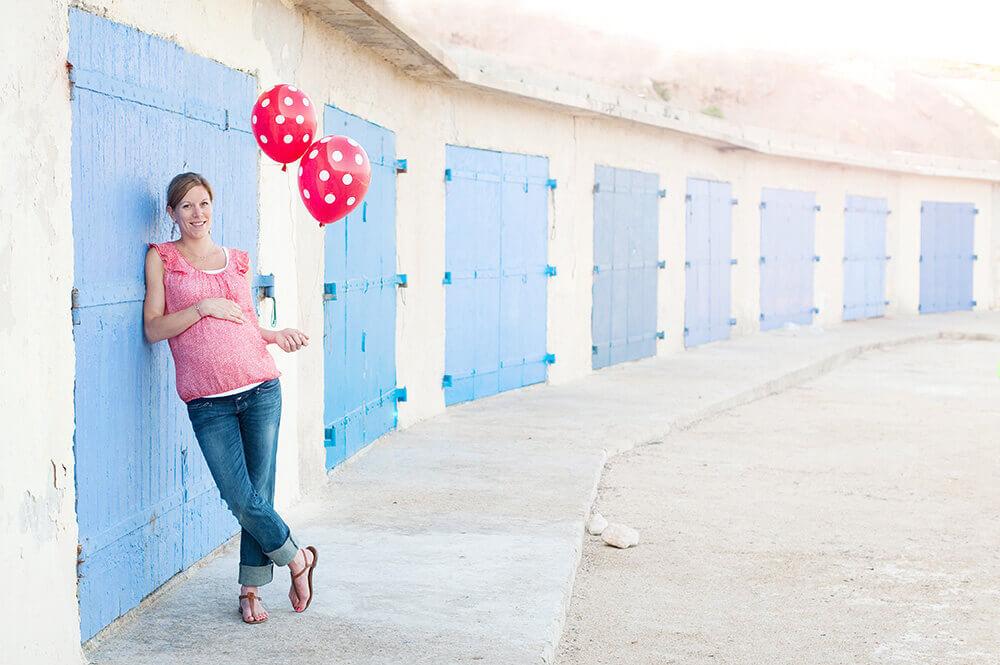 Femme enceinte tenant des ballons rouges hélium devant des portes bleues.