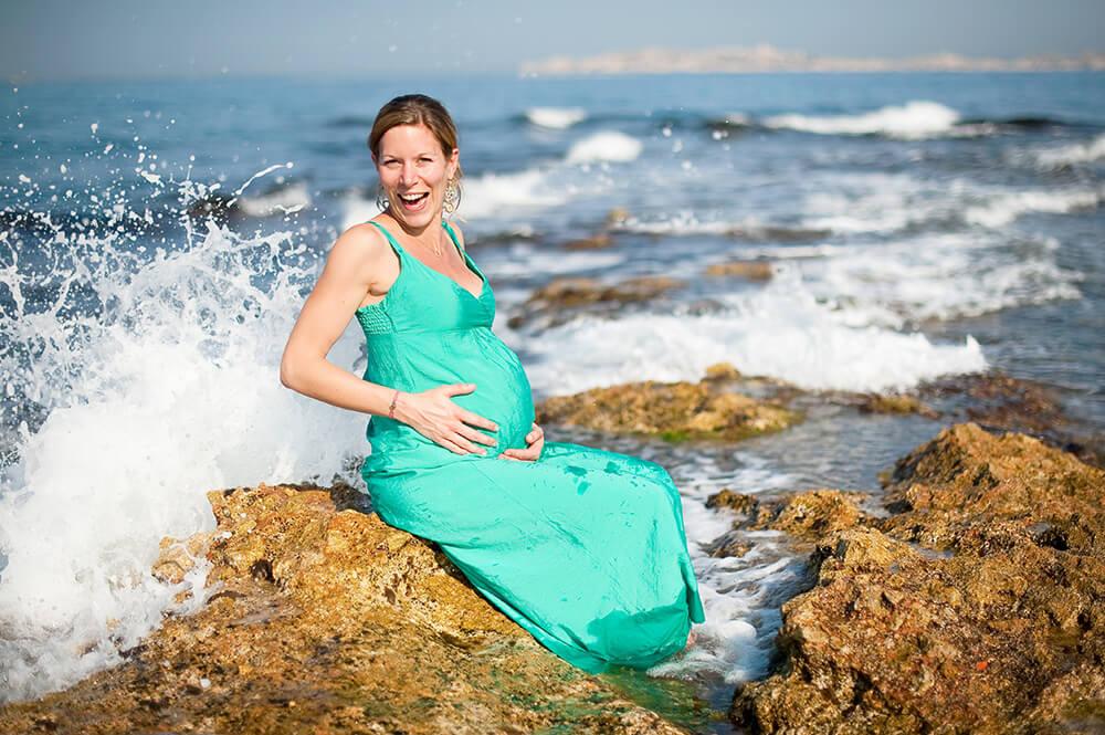 Femme enceinte assise sur un rocher et se faisant trempée.