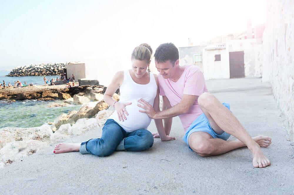 Couple assis par terre avec les mains sur le ventre tout rond de la femme enceinte