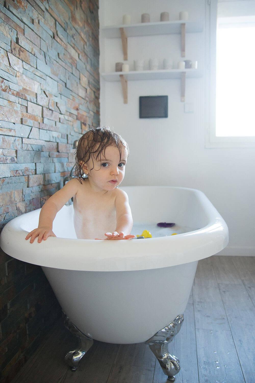 Portrait de bébé debout dans sa baignoire.