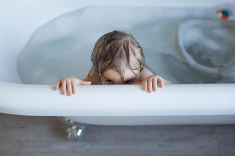 Portrait de bébé entrain de jouer dans son bain.