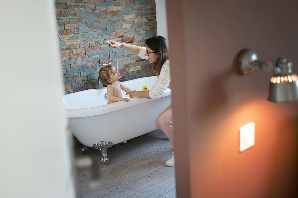 Maman qui douche son enfant.
