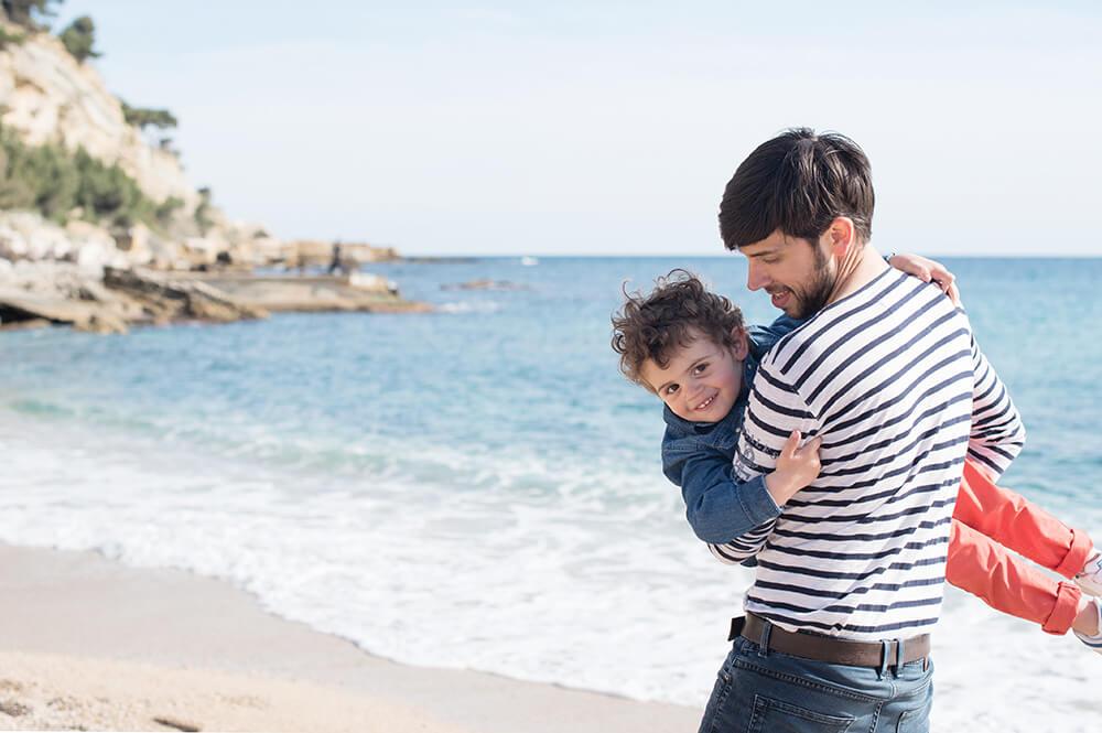 Môme dans les bras de son père jouant sur la plage.