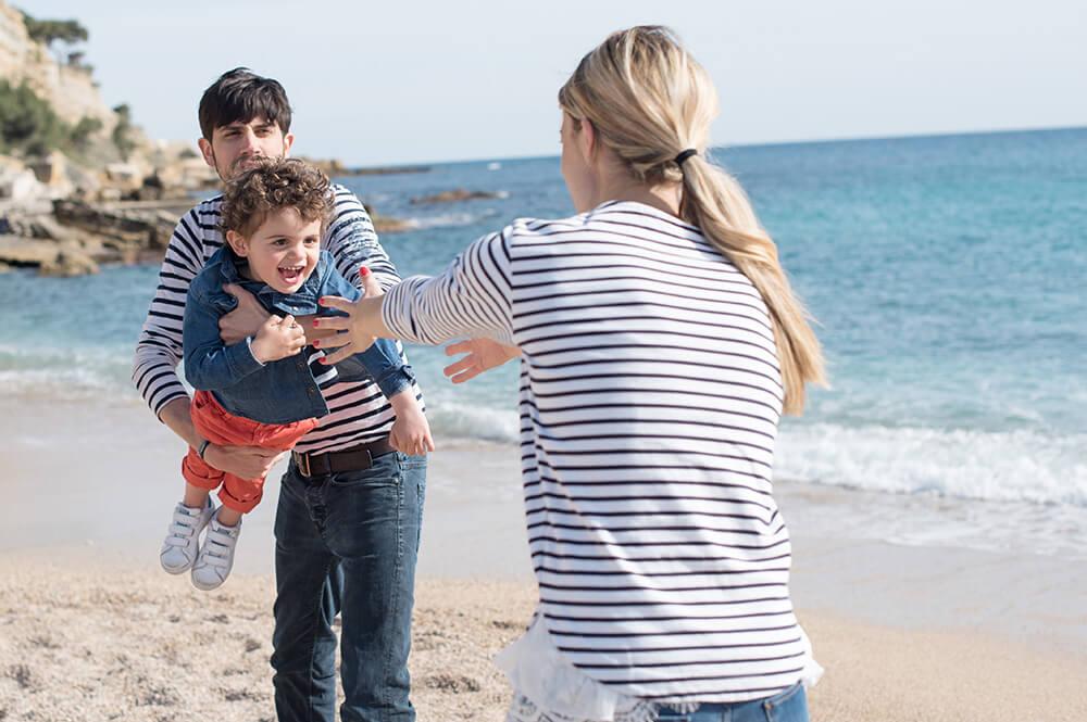 Parents qui jouent avec son enfant sur la plage.