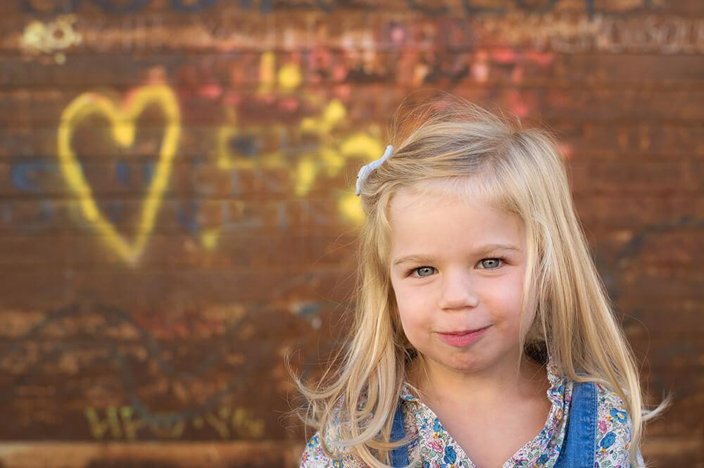 Portrait de gamin devant mur graffitis.