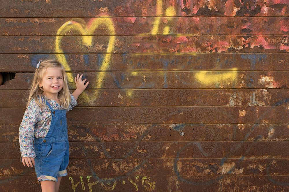 Portrait d'enfant devant un rideau de fer
