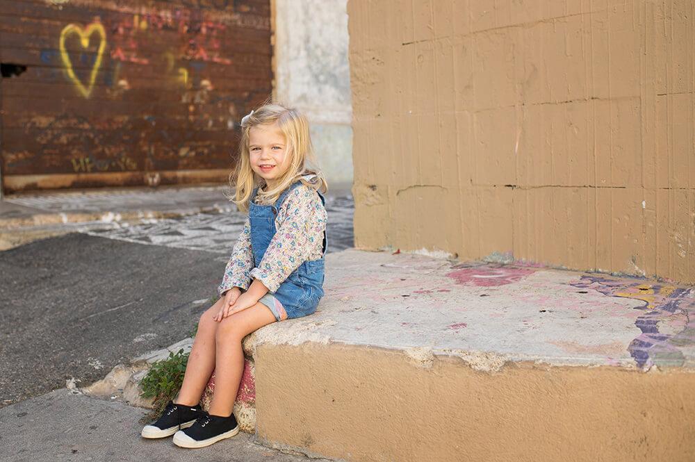 Petite fille assise au coin d'une rue