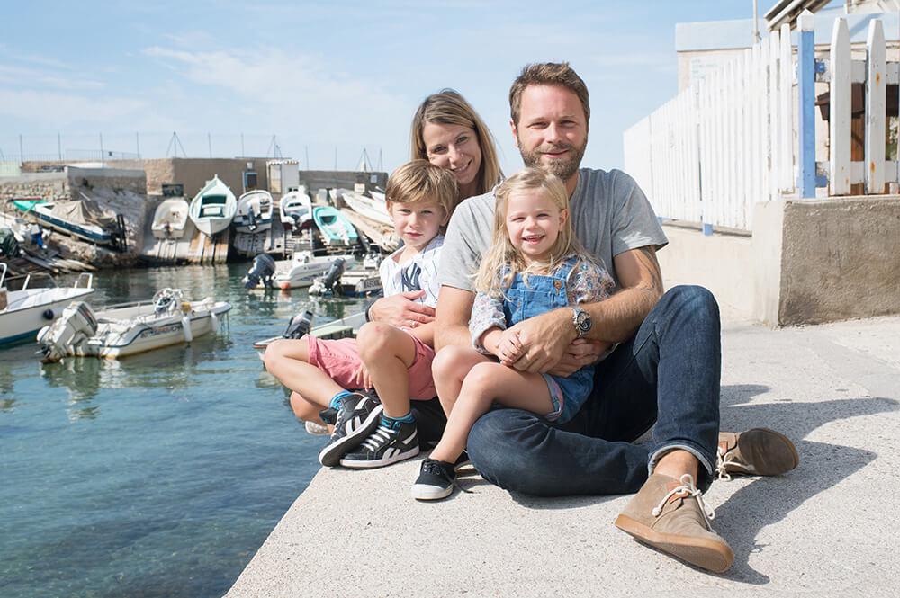 Photo de famille assise au bord de l'eau