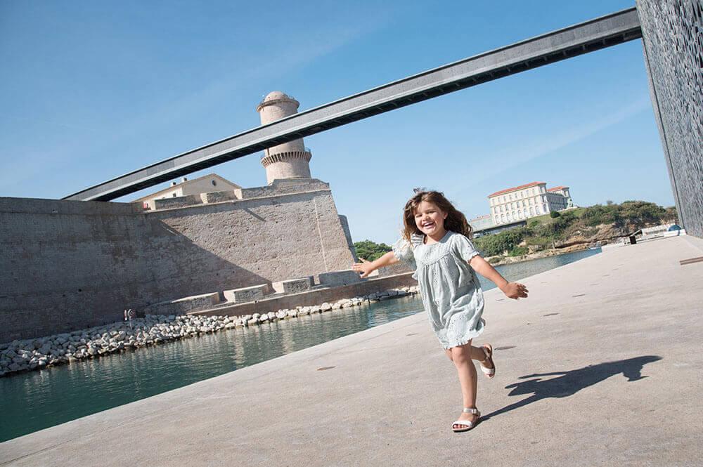 Portrait d'une enfant entrain de courir devant le MuCem.