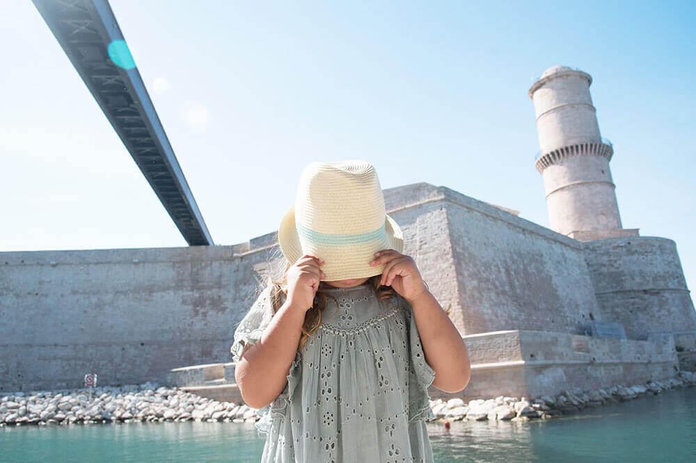 Photo d'une enfant avec un chapeau de paille devant le Fort Saint Jean.