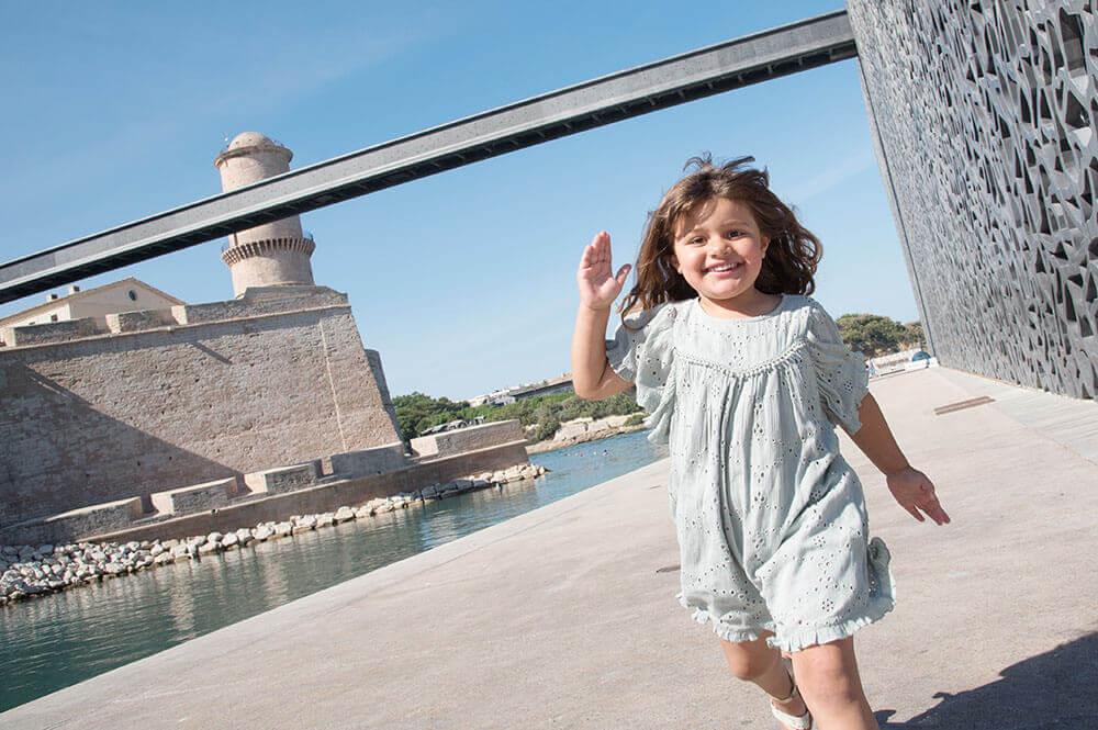 Photo d'une jeune fille entrain de courir sur la parvis du MuCem.