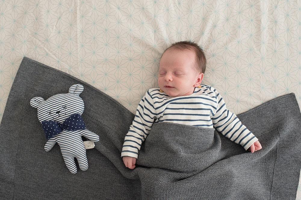 Baby avec son doudou. Tous les deux habillés avec des rayures bleues.