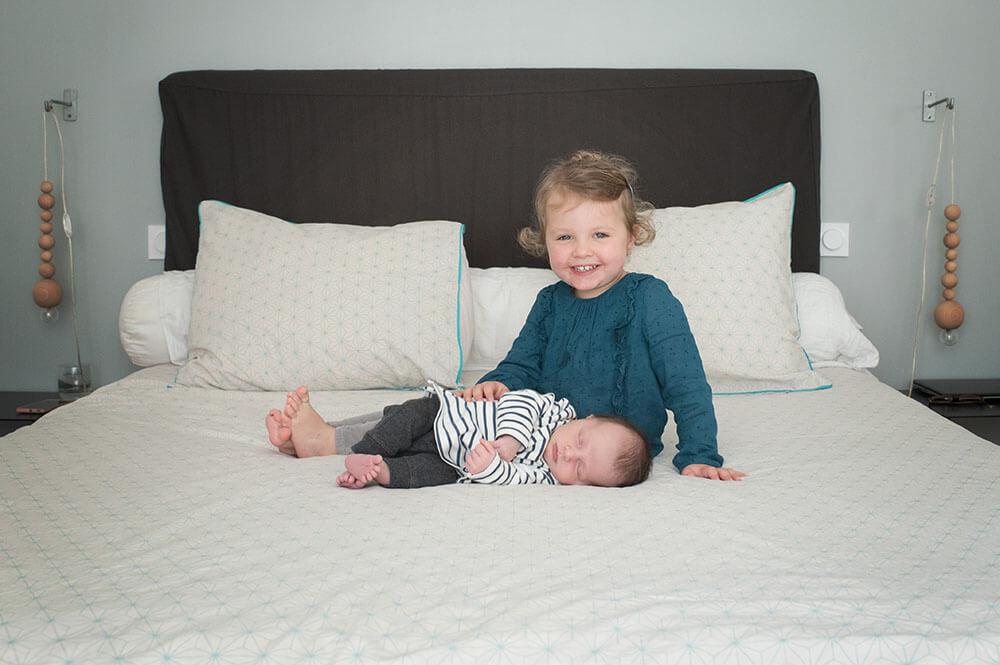 Sieste de bébé à côté de sa grande sœur très souriante.