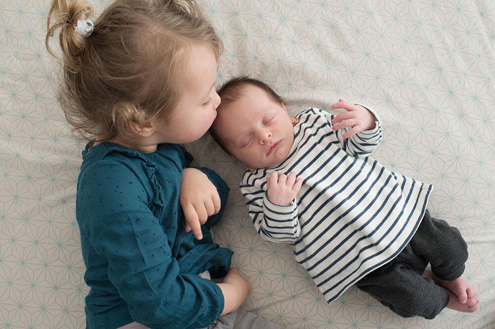 Bisous sur le front de son tout-petit frère.
