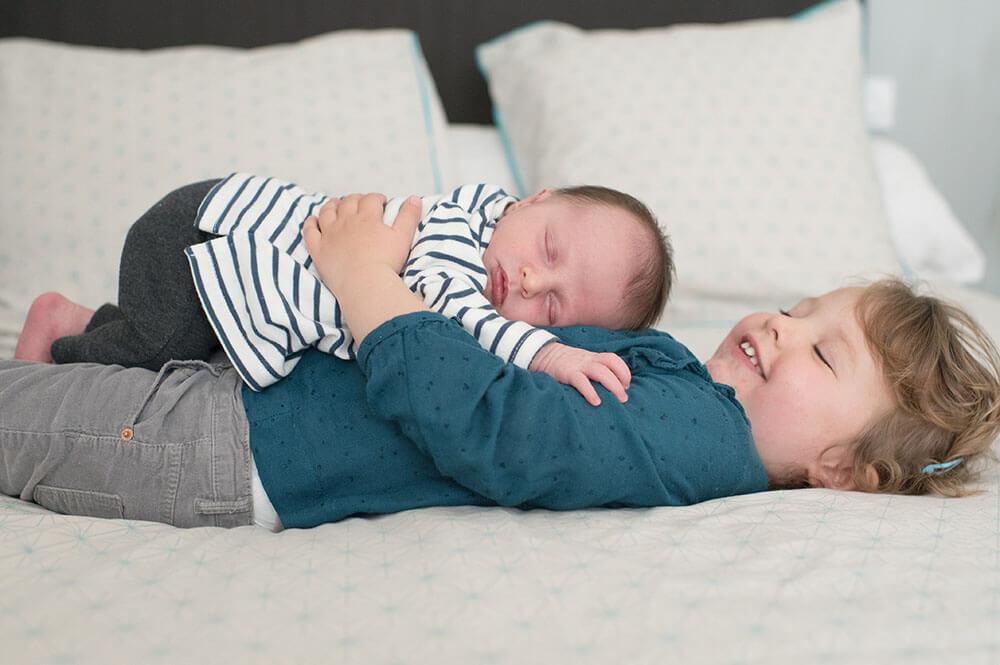 Portrait bébé sur le ventre de sa grande sœur.
