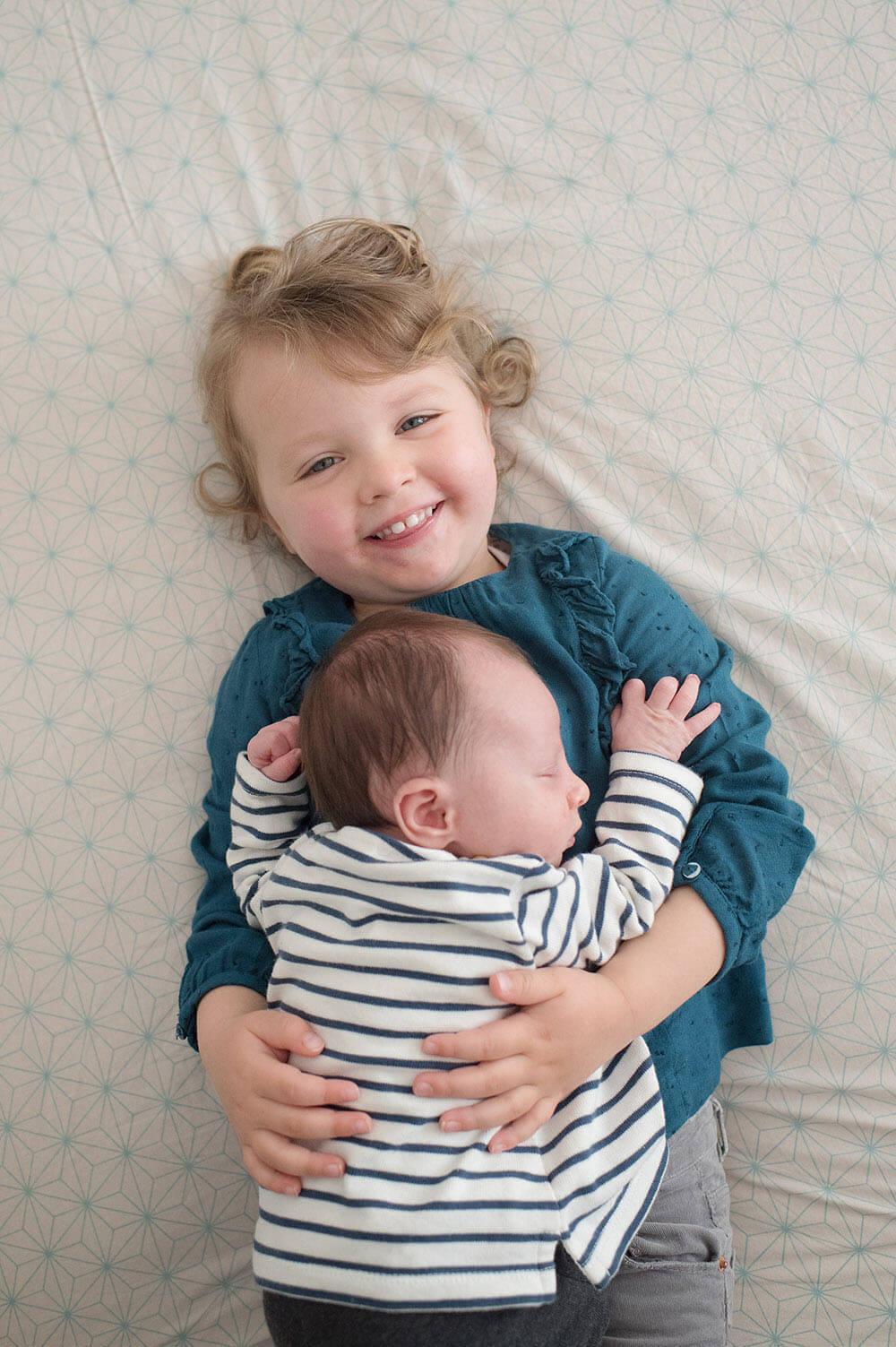 La grande sœur qui porte son petit frère sur le lit.