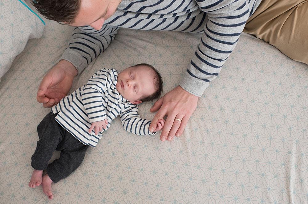 Portrait nouveau-né tenant un doigt de la main de son papa.