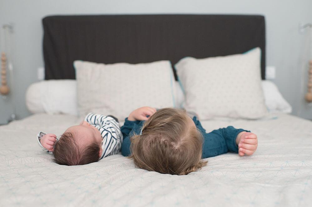 Petit frère et grande sœur allongés sur le lit des parents
