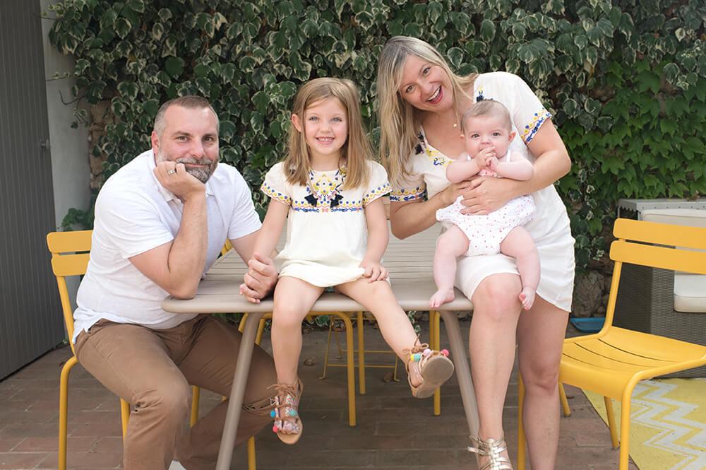 Portrait de famille assis sur une table de jardin.
