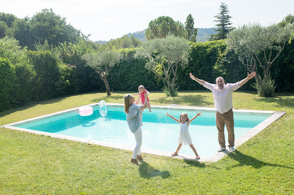 Séance photo famille à domicile à Ventabren. Portrait de famille au bord de la piscine.