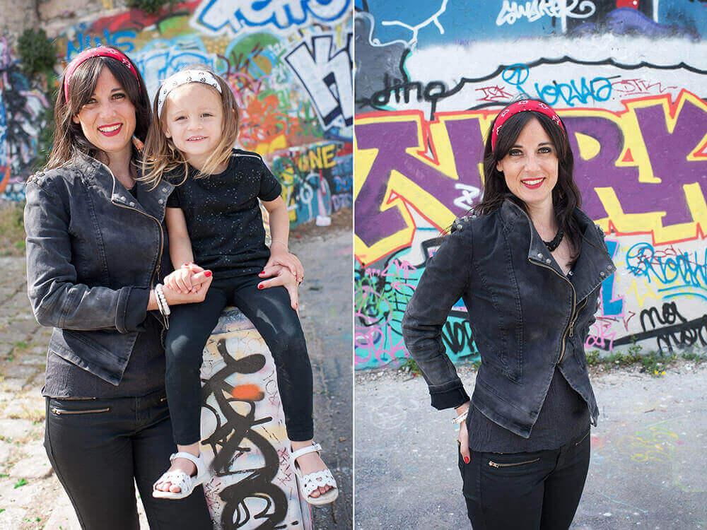 Portrait d'une enfant sur un muret devant un mur de graffitis.