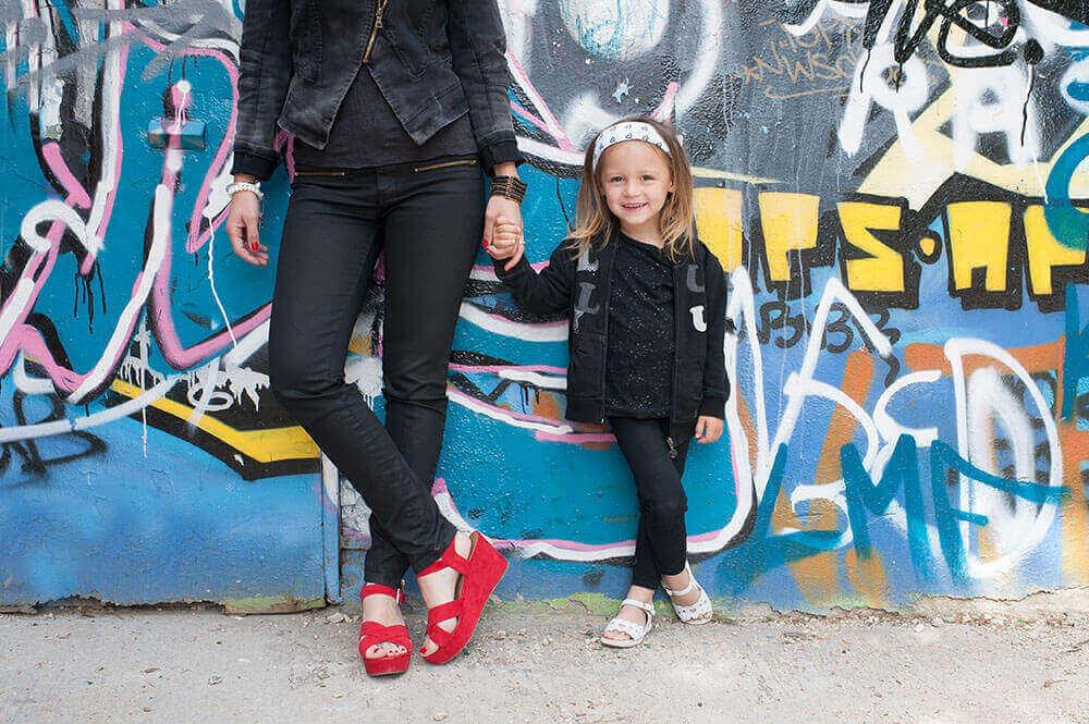 Portrait d'enfant qui tient la main de sa mère devant un mur rempli de graffitis