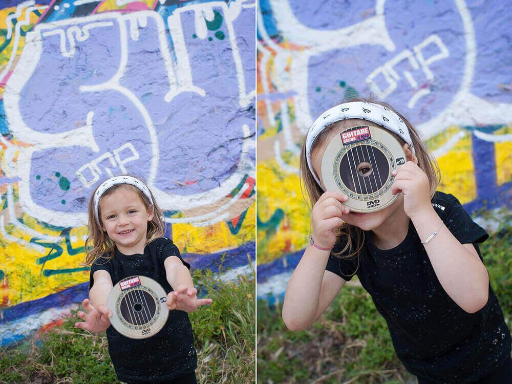 Portrait d'enfant entrain de jouer avec un CD devant un mur de graffitis