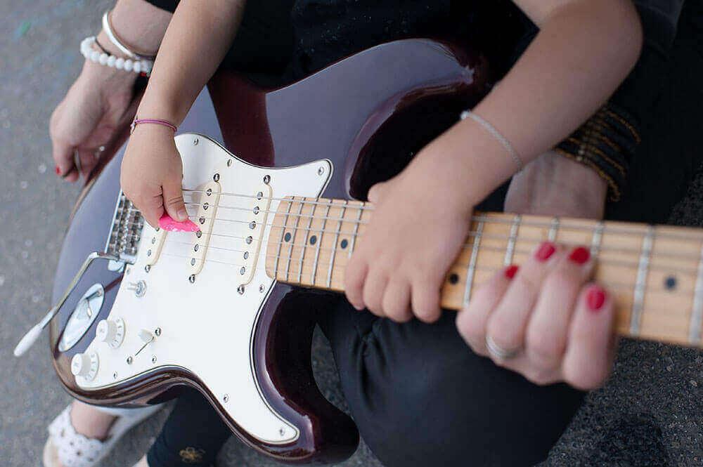 Enfant entrain de jouer de la guitare électrique.