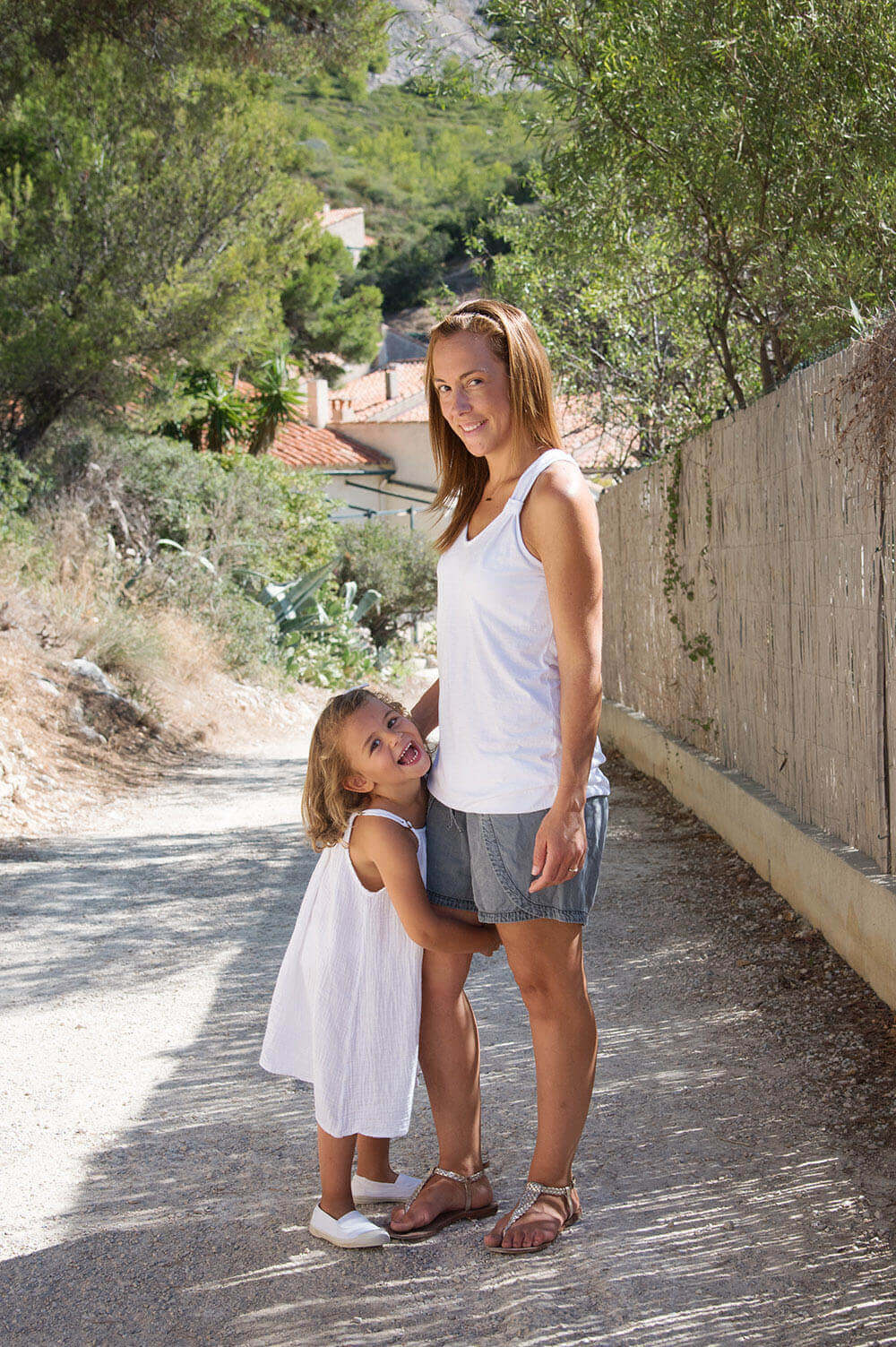 Photo en extérieur d'une maman et de sa fille qui lui tient la jambe. Séance photo à Sormiou.