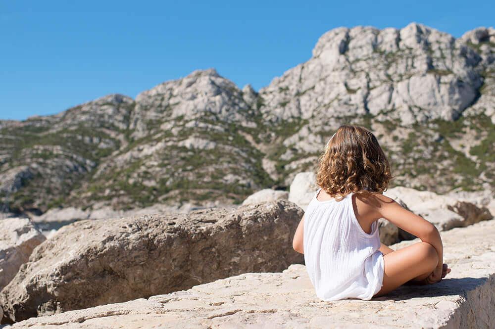 Dos d'enfant. Assise sur un muret devant la montagne