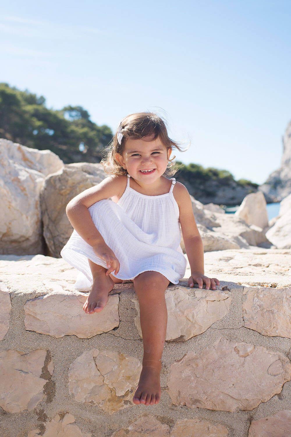 Portrait d'enfant pied nu assise sur un muret avec un grand sourire