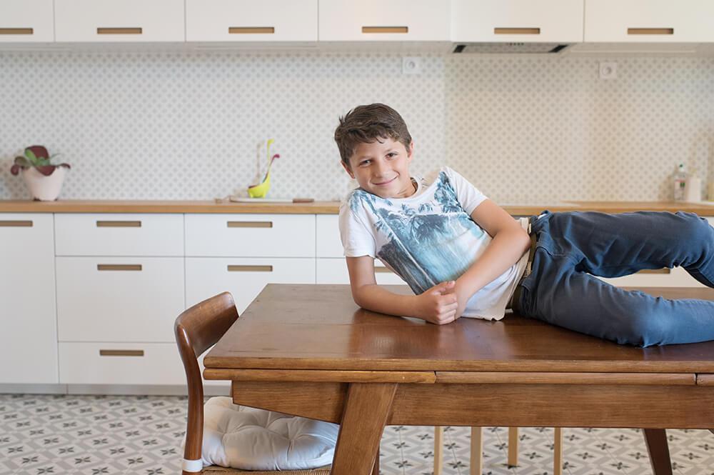 Portrait d'un adolescent allongé sur une table de cuisine.