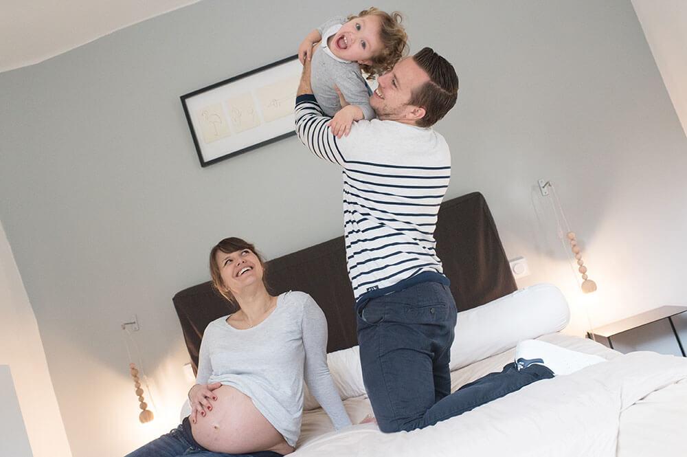 Papa qui joue avec sa petite fille sur son lit.