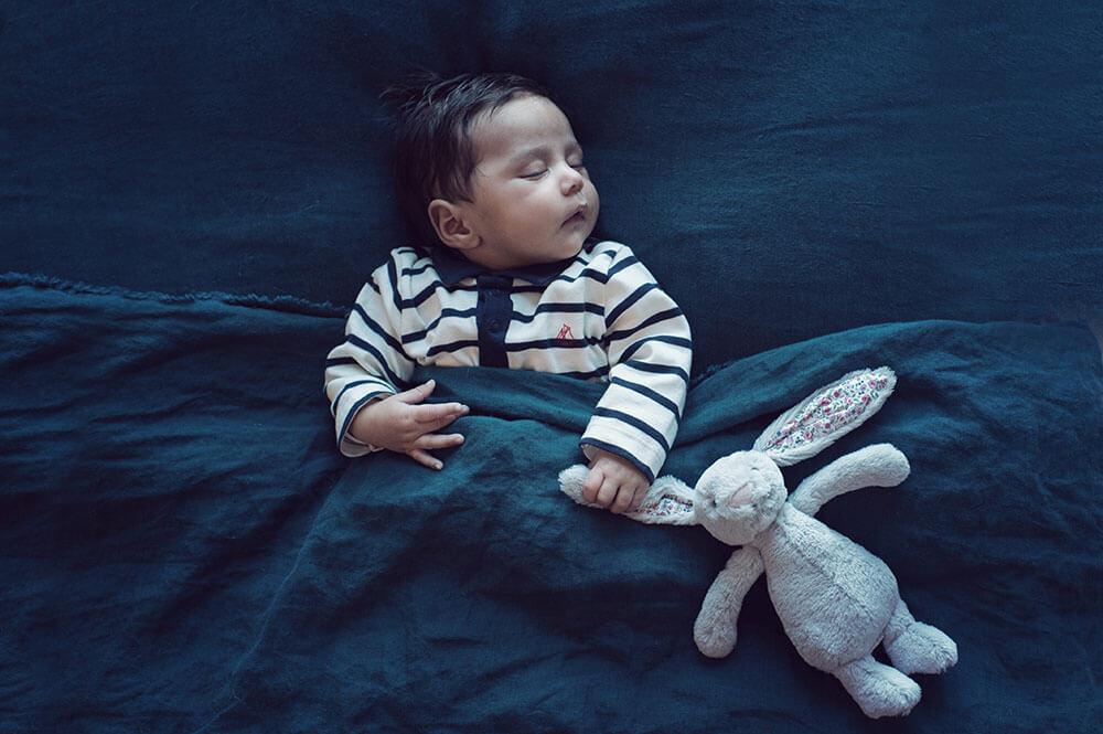 Nouveau-né entrain de dormir avec son doudou