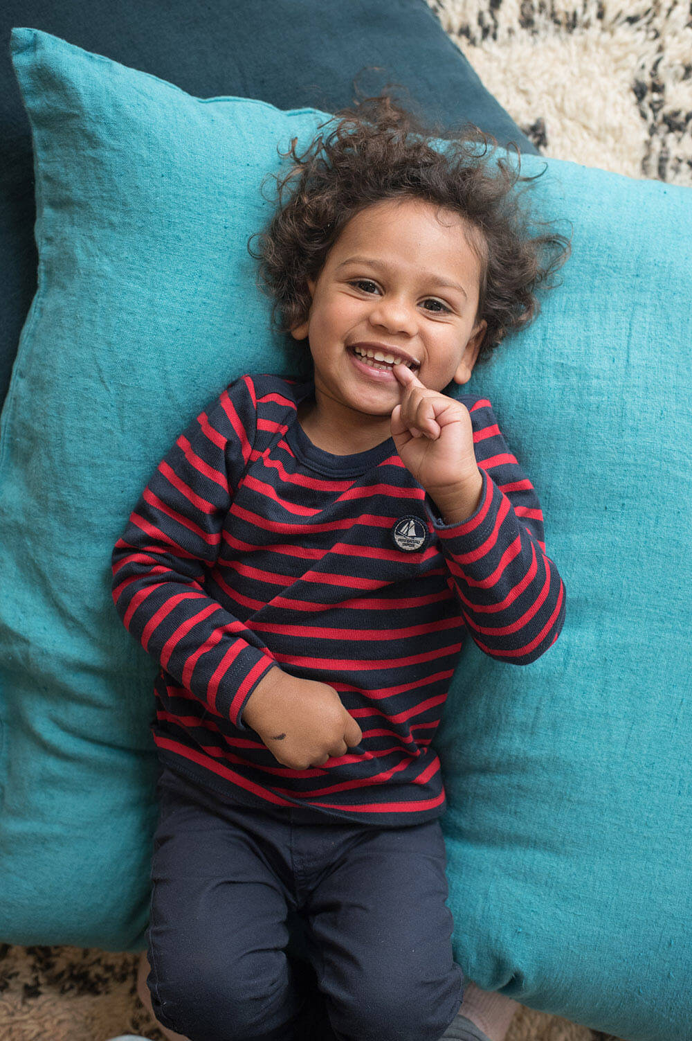 Portrait enfant avec une marinière bleu et rouge.