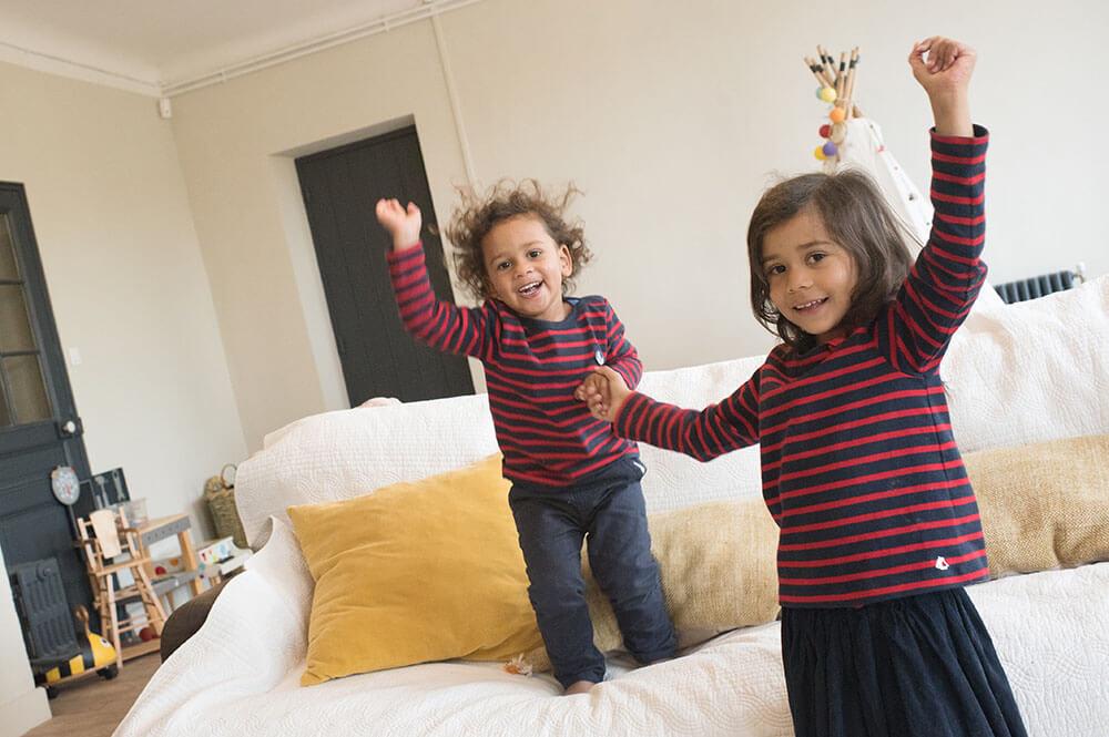 Frère et sœur sautant main dans la main.