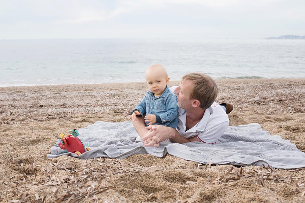 Bambin et son papa allongés sur une couverture sur le sable.