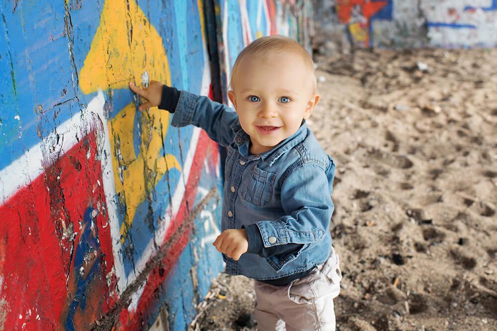 Portrait d'un tout petit devant des graffitis rouges.