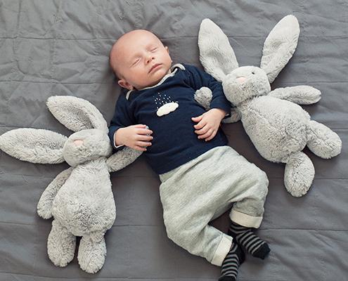 Séance naissance à la maison. Nouveau-né avec ses deux lapins de chaque coté. Photo rigolote. moment-photo