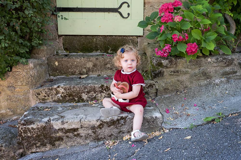 Portrait enfant sur des marches en pierres.