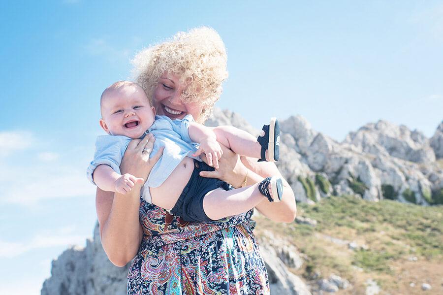 Portrait jouant avec son bébé avec un ciel bleu.