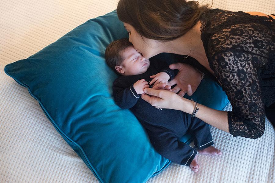 Maman faisant un bisou sur le front de son nouveau-né.