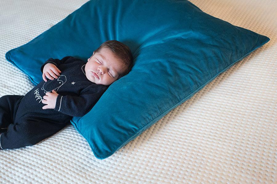 Bébé faisant sa sieste sur coussin bleu électrique.