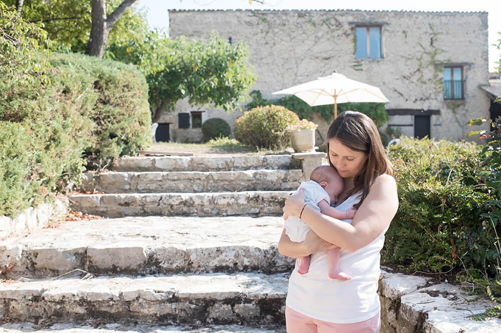 Portrait nouveau-né dans les bras de sa maman devant une jolie demeure
